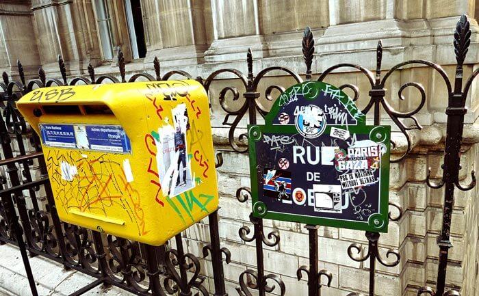 落書きだらけの黄色いポストと住所プレート